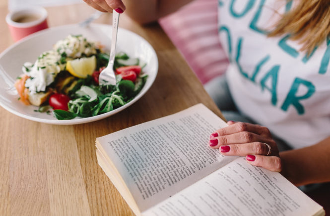 Eating fresh breakfast and reading book in morning